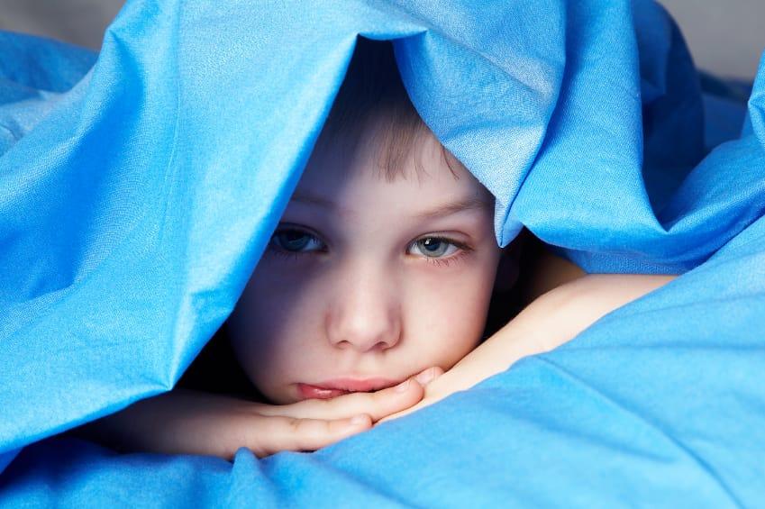 sleepy boy in blue bedclothes