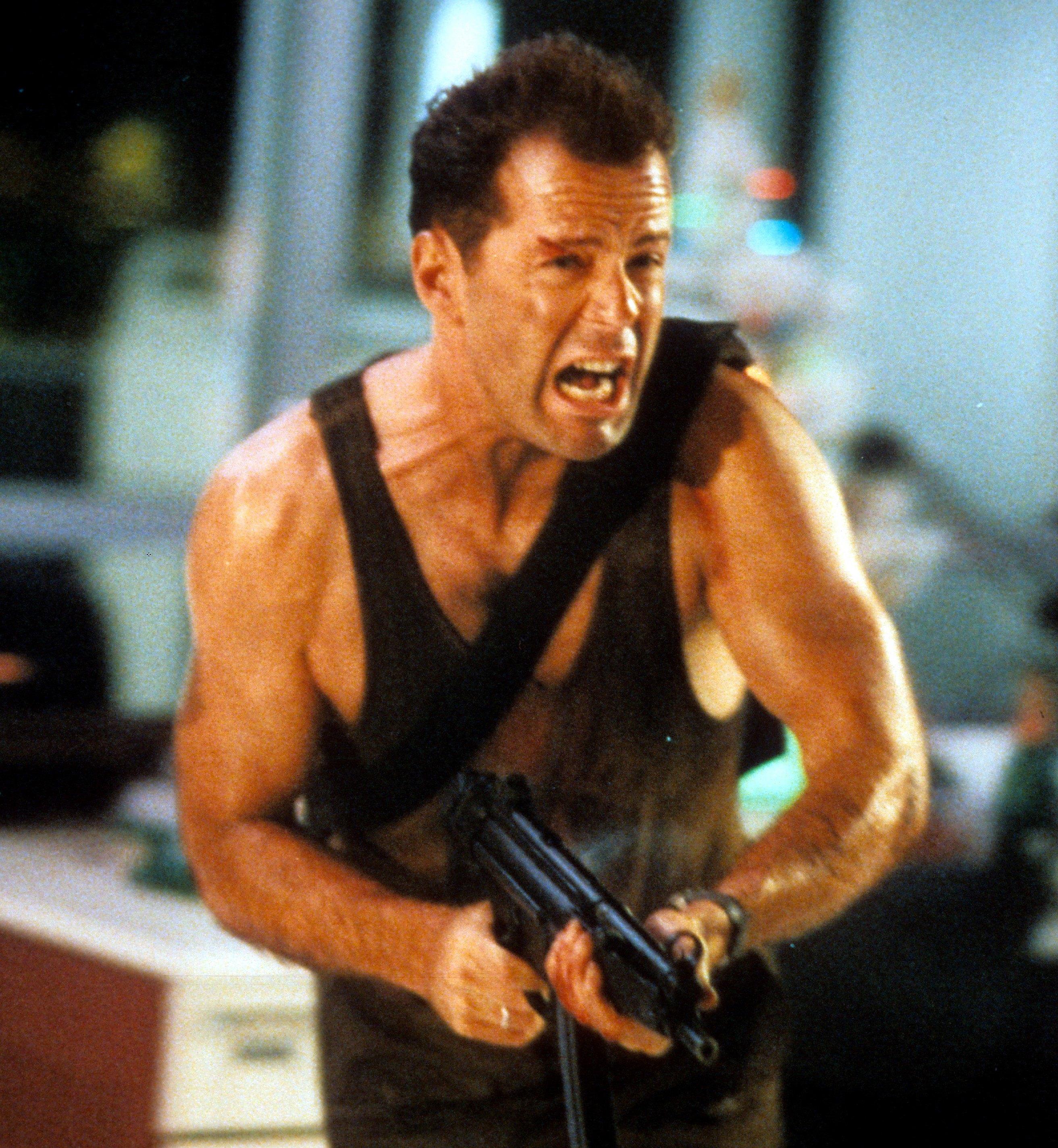 Bruce Willis wielding a machine gun as John McClane in Die Hard 1988