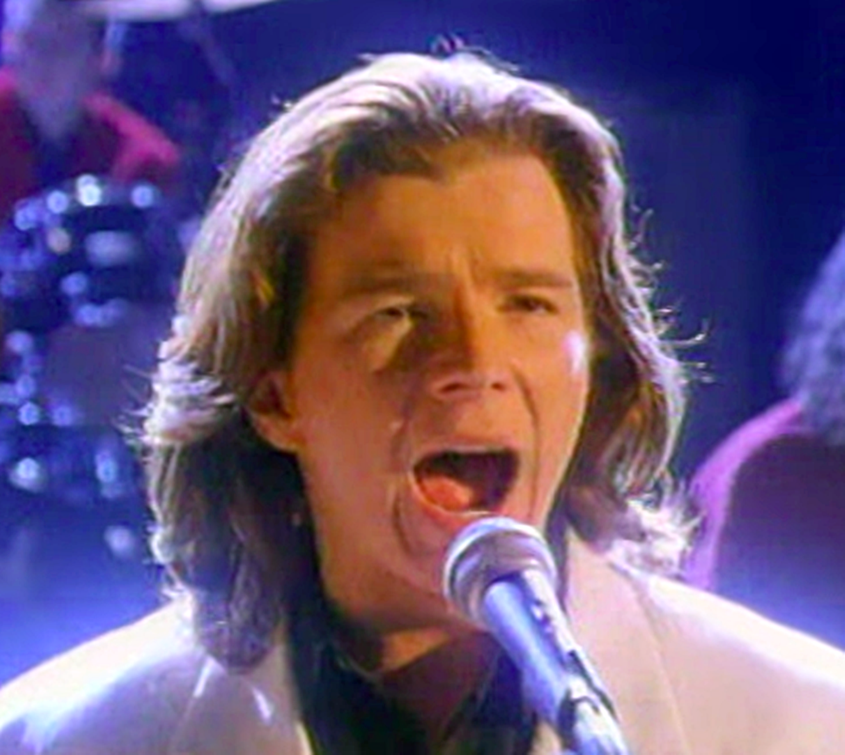 Astley performing live on stage