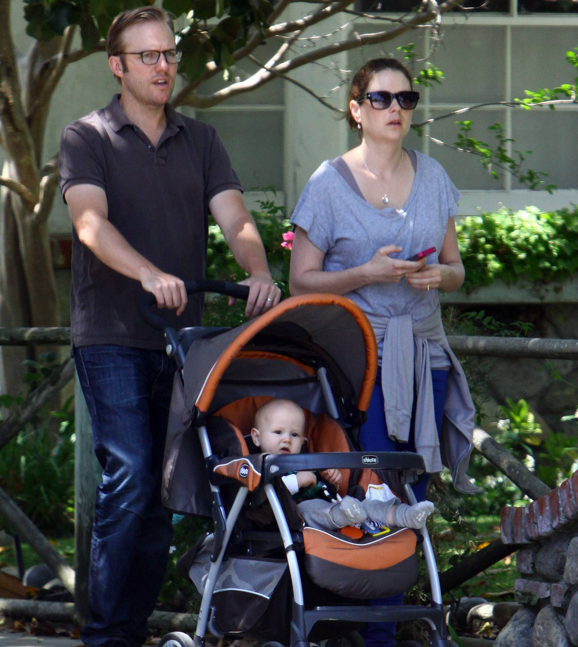 Jenna Fischer walking with husband Lee Kirk and son Weston Lee Kirk in a stroller, 2012
