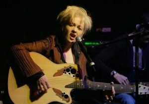 Cyndi Lauper performing at a live gig, singing and playing guitar