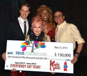 Cyndi Lauper holding a giant cheque from the True Colours Fund