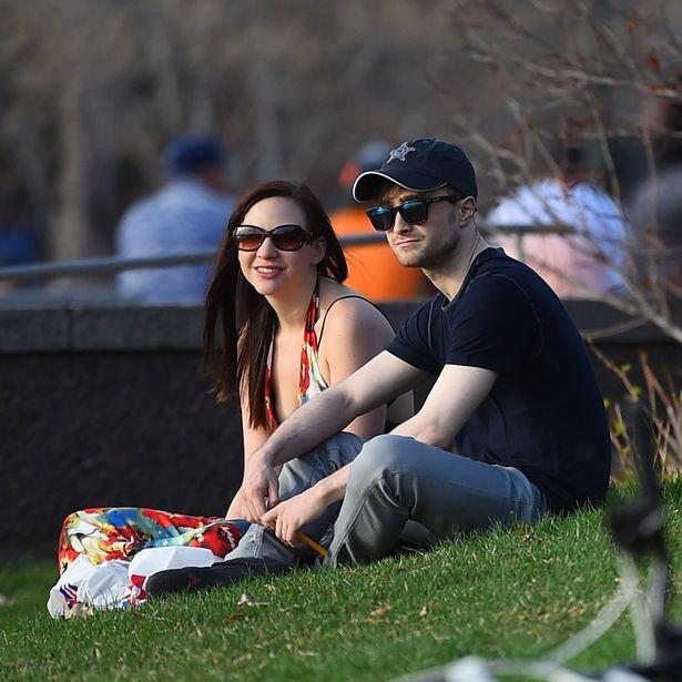 Daniel Radcliffe with fiancee Erin Darke sitting in a park