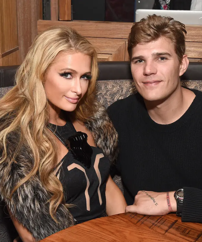 Paris Hilton and fiancé Chris Zylka sit at a table