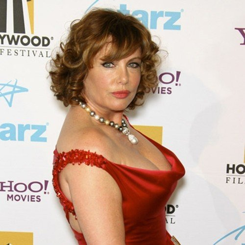 Kelly LeBrock now, wearing a red dress and pearl necklace