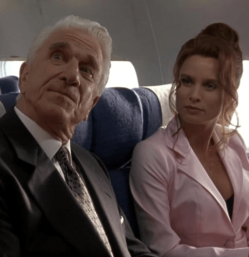 Leslie Nielsen on a plane with Nicollette Sheridan as Dick Steele and Veronique Ukrinsky in Spy Hard, 1996