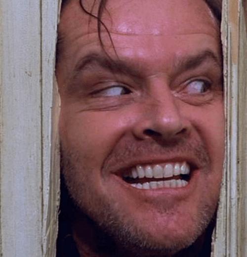 Jack Nicholson peering through the door as Jack Torrance in The Shining, 1980