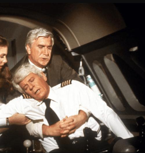 Leslie Nielsen as Dr Rumack carrying Peter Graves as Captain Oveur in Airplane!, 1980