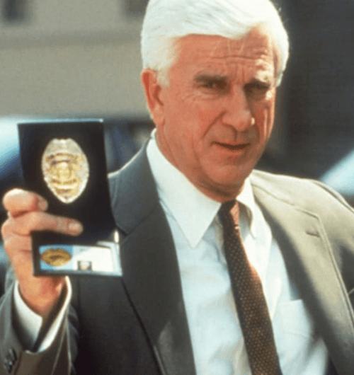 Leslie Nielsen flashing his police badge as Frank Drebin in The Naked Gun, 1988