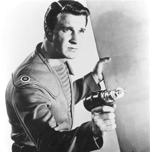 A young Leslie Nielsen wielding a ray gun as Commander John Adams in Forbidden Planet, 1956