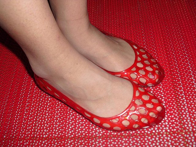 Woman wearing red jelly shoes 90s Fashion Trends That Should Never Come Back